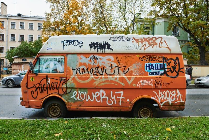 Oude gebroken oranje die bestelwagen volledig met graffiti wordt doorzeefd royalty-vrije stock foto