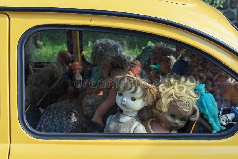 Oude gebroken poppen achter het glas van een auto De poppen van de Grungestijl royalty-vrije stock afbeelding