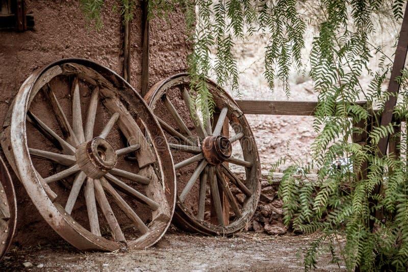 Oude gebroken wagenwielen die tegen een muur leunen royalty-vrije stock fotografie