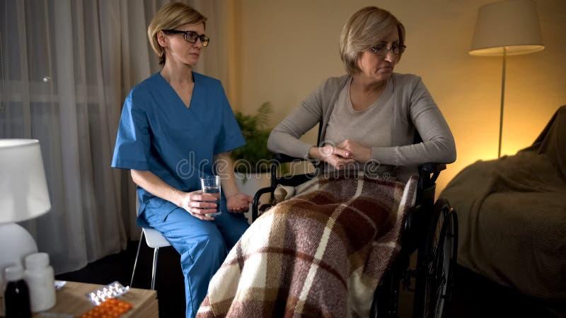 Oude gedeprimeerde dame die geneeskunde van verpleegstershanden weigeren te nemen, het verouderen droefheid royalty-vrije stock foto