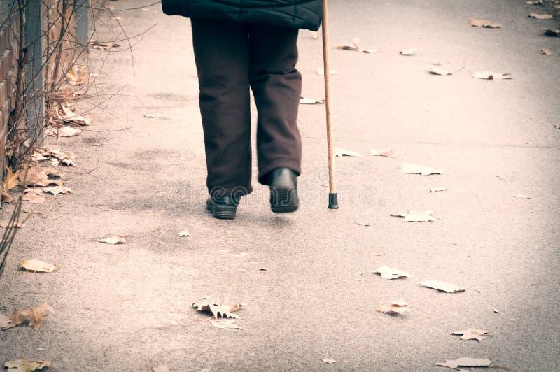 Oude gedeprimeerde vrouwengang alleen onderaan de straat met wandelstok of rietgevoels eenzame en verloren mening van rug stock fotografie