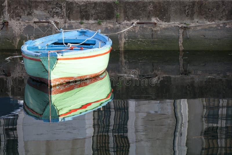 Oude gekleurde houten boot in het water in een rivier met bezinning royalty-vrije stock afbeeldingen