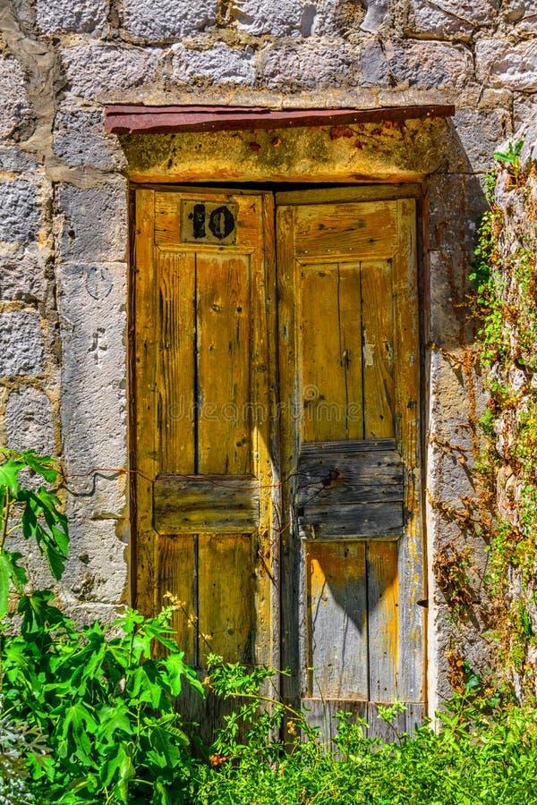 Oude gele deur op het steenhuis stock foto