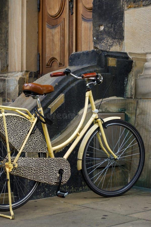 Oude gele fiets leerzetel met schokbrekers en wiel voor een kerk royalty-vrije stock afbeeldingen