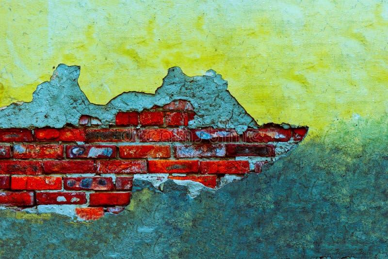 Oude gele gepleisterde muur met bakstenen en gebroken gipspleister Oude gele muur met bakstenen en gebroken pleister stock foto
