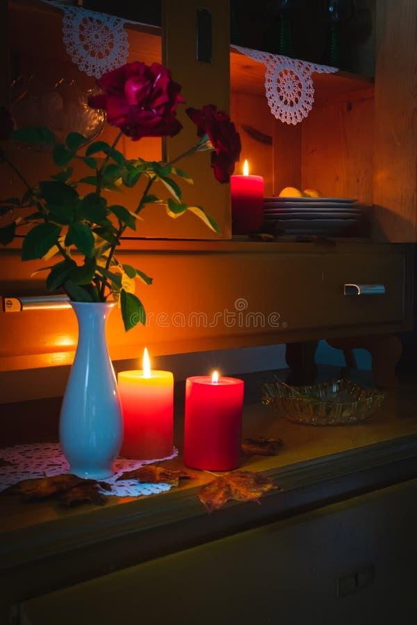 Oude gele geschilderde kast met kaarsen, een vaas met rode rozen, de herfstbladeren en gehaakte doilies stock fotografie