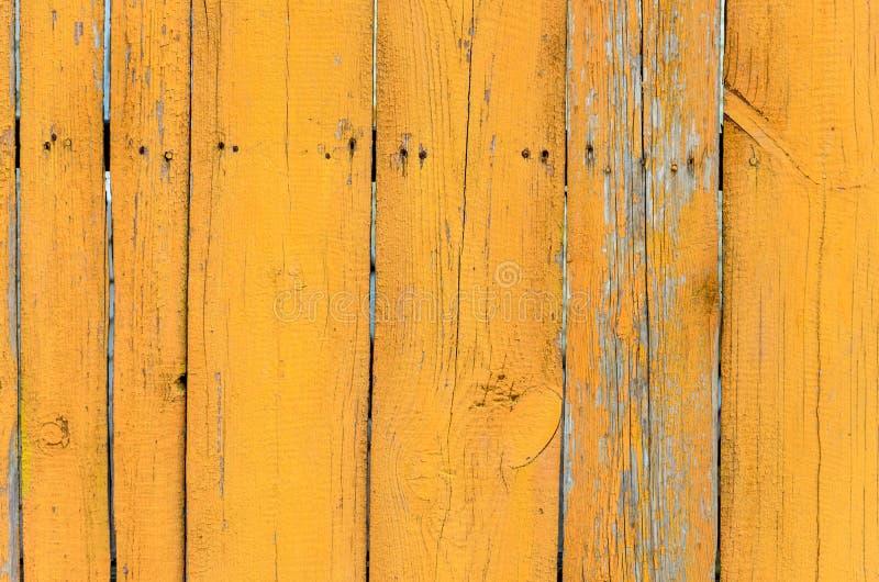 Oude gele houten muur met gebarsten verflaag, gedetailleerde achtergrondfototextuur stock foto's