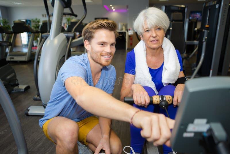 Oude gelukkige vrouw die op het roeien machine in gymnastiek uitoefenen stock afbeeldingen