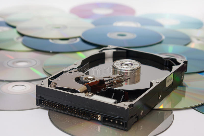 Oude geopende harde schijf op een stapel van compact-discs stock foto