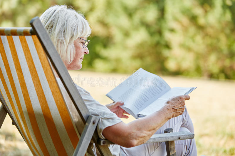 Oude gepensioneerdelezing in de zomer stock foto