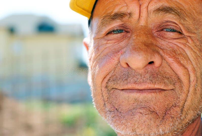 Oude gerimpelde mens met geel GLB royalty-vrije stock fotografie