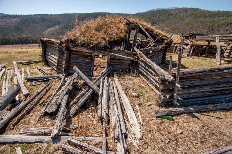 Oude geruïneerd houten yurt In de voorgrond rotte logboeken stock foto's