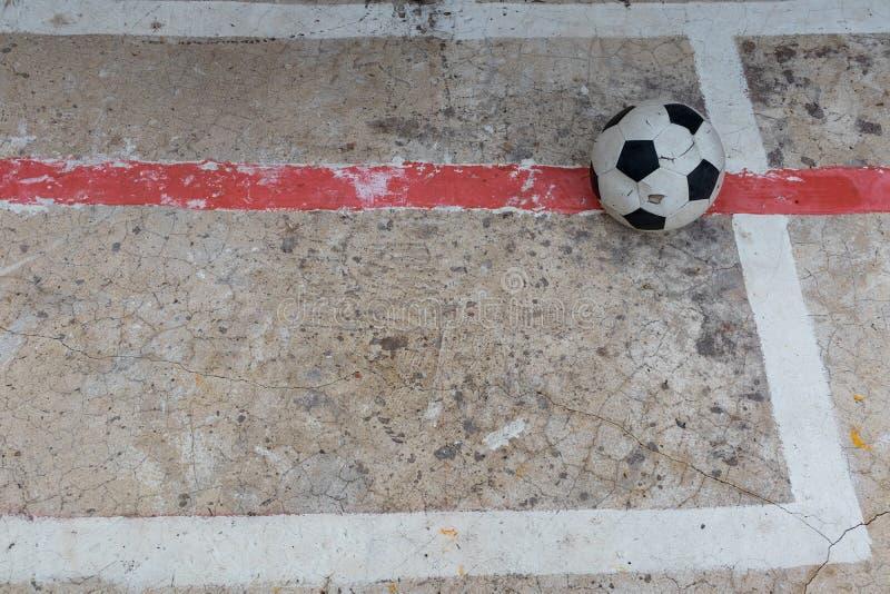 Oude geruïneerde beschadigde voetbalbal gezet op gebarsten cementgebied stock foto