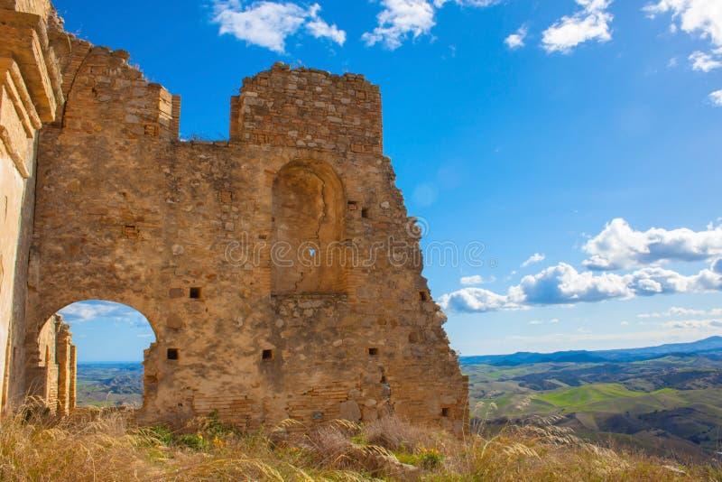 Oude geruïneerde muur tegen de blauwe hemel in Craco, Italië stock foto