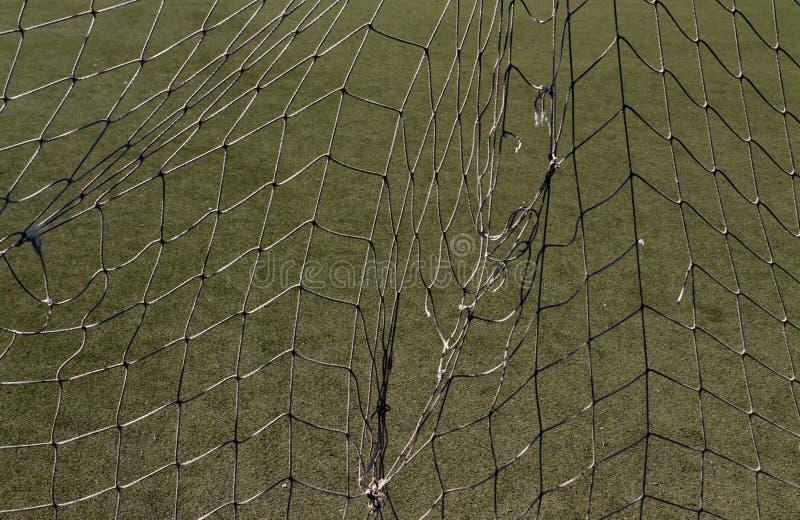 Oude gescheurde voetbal netto tegen groene lening stock afbeelding