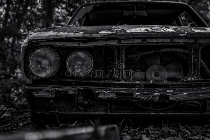 Oude gesloopte auto in zwart-witte scène Verlaten roestige auto in het bosclose-up vooraanzicht van rotte en roestige gesloopte a royalty-vrije stock fotografie
