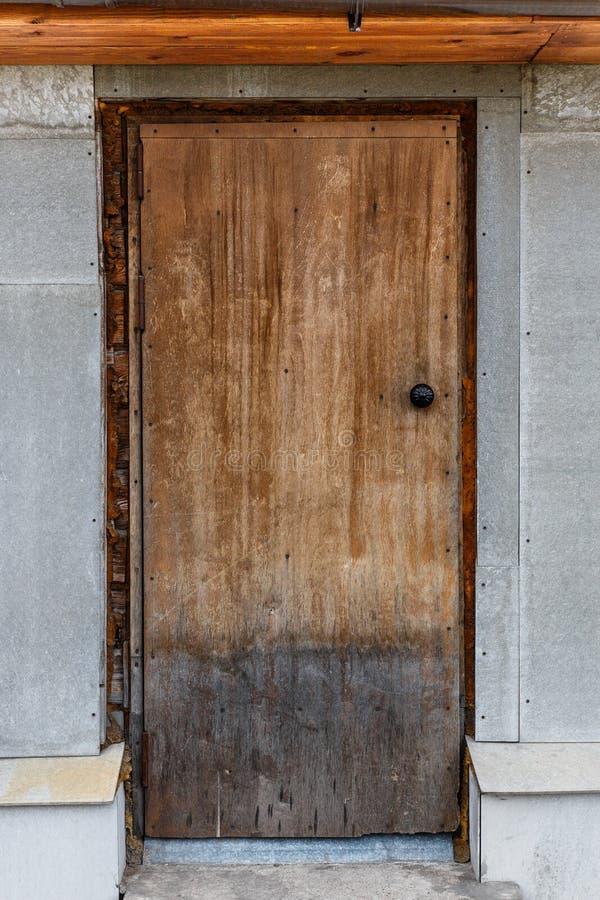 Oude gesloten houten deur Een schil, gebarsten, lichtbruine deur stock foto