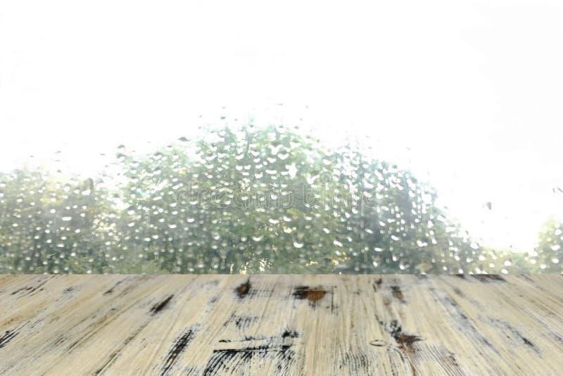 Oude gewassen eiken houtlijst aangaande de onscherpe daling op vensterachtergrond, houten lijst stock foto