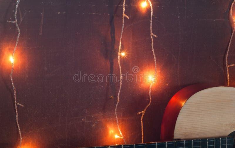 Oude gitaar op de achtergrond van Kerstmislicht, royalty-vrije stock afbeelding