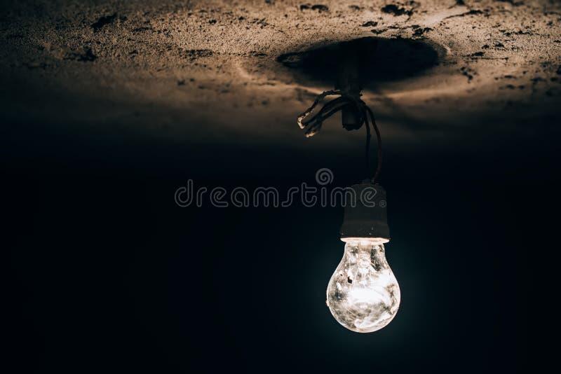 Oude gloeilamp die in de donkere kelderverdieping gloeien elektriciteitsimprovisatie bij bouwwerf stock afbeelding