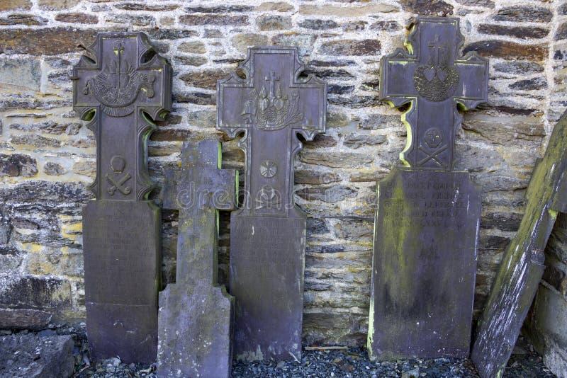 Oude grafstenen die tegen buitenkerkmuur leunen stock afbeelding