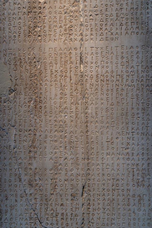 Oude Griekse die woorden in steen met gebarsten worden gesneden stock afbeelding