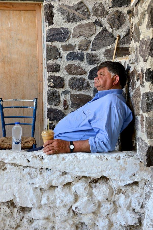 Oude Griekse mensenzitting buiten zijn huis, het drinken koffie stock afbeeldingen