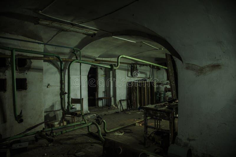 Oude griezelige kelderverdieping van verlaten asiel Oude rotte boiler, het verwarmen pijpen stock foto's