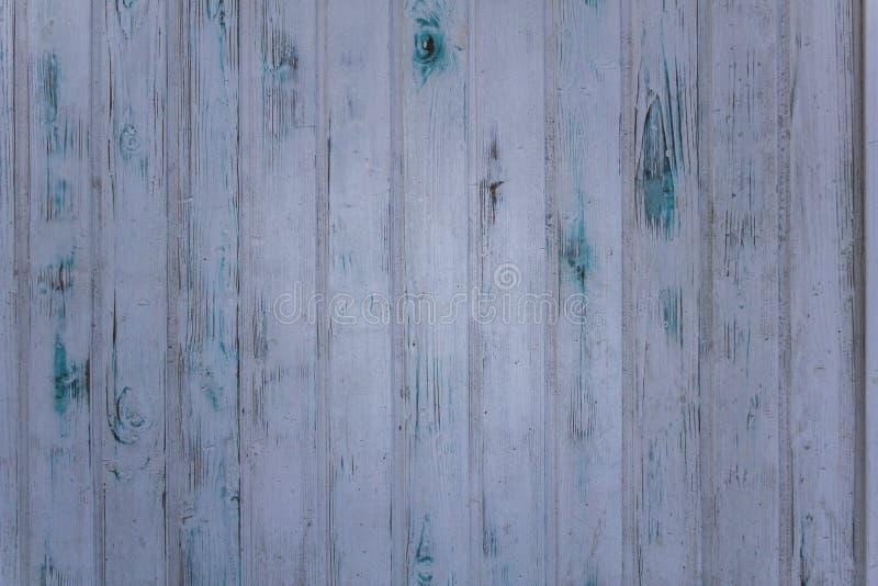 Oude grijs-witte muuromheining van houten planken met krassen en groenachtig blauwe vlekken van verf Verticale lijnen Ruwe Opperv royalty-vrije stock afbeeldingen
