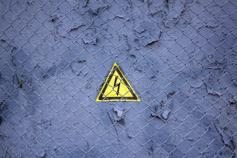 Oude grijze blauwe muur met schilverf onder een metaalnet met een driehoekig geel teken van gevaarlijk elektrovoltage ruw royalty-vrije stock afbeeldingen