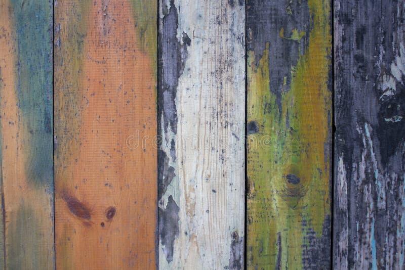 Oude grijze houten muuromheining van multi-colored raad met schil witte, groene en rode verf Verticale lijnen Ruwe Oppervlaktetex stock afbeeldingen