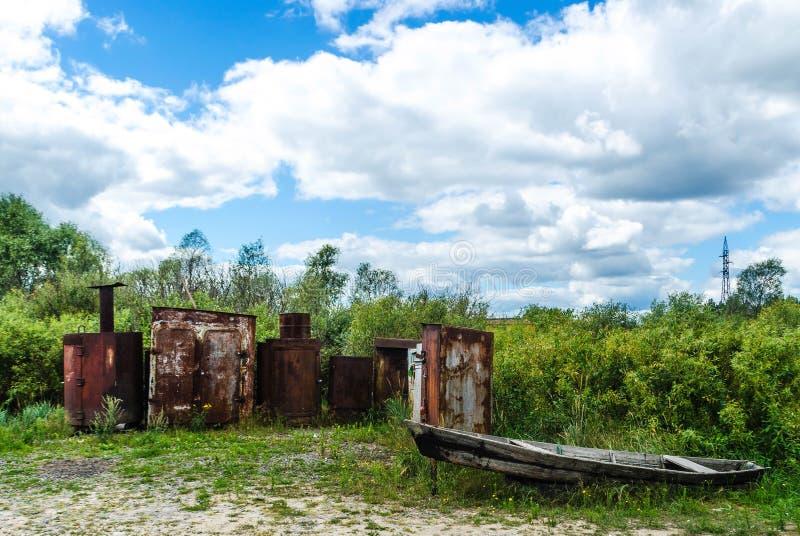 Oude grijze houten verlaten vissersboot op de achtergrond van roestige metaaldozen royalty-vrije stock foto