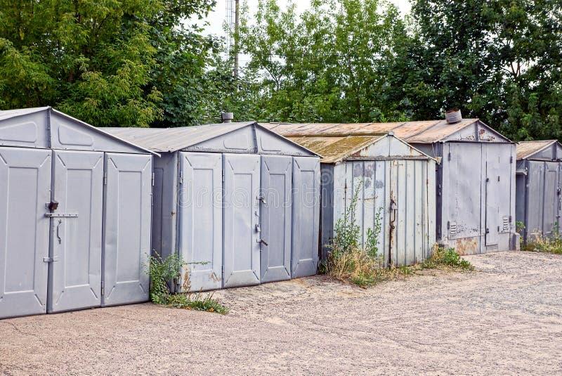 Oude grijze ijzergarages in het struikgewas van gras dichtbij de weg royalty-vrije stock afbeelding