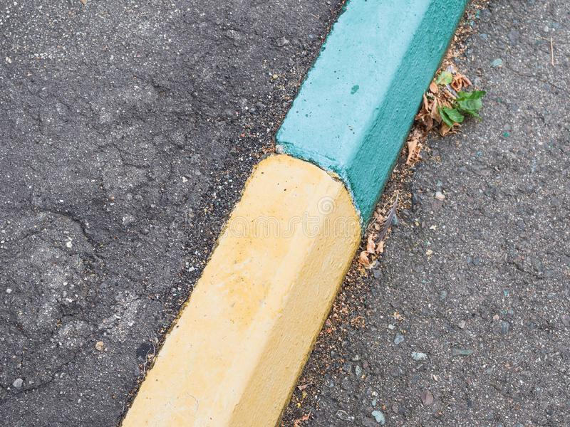Oude groene en gele geschilderde kerbstone stock foto's