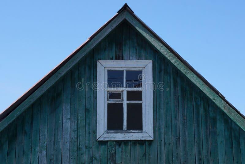 Oude groene houten zolder met wit venster tegen de blauwe hemel stock afbeeldingen