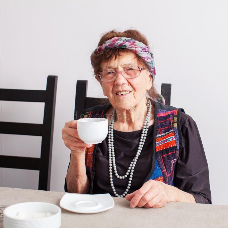 Oude grootmoeder het drinken thee stock fotografie