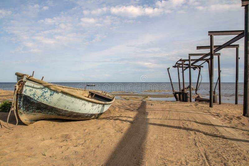 Oude grote vissersboot op de achtergrond van het overzees, het zand en het gebroken Telfer-viaduct voor de lancering van boten in stock foto's