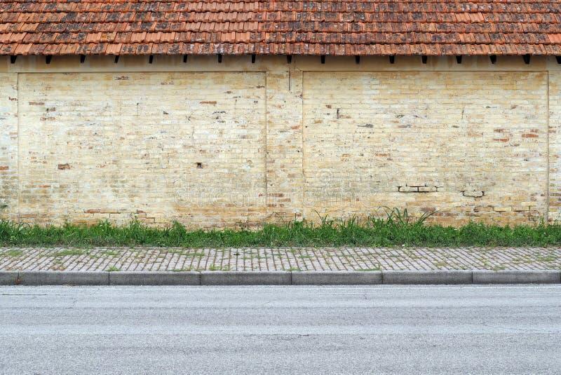 Oude grunge gele bakstenen muur met terracotta betegeld dak Een streep van gras, betontegel stoep en asfaltweg vooraan royalty-vrije stock afbeelding