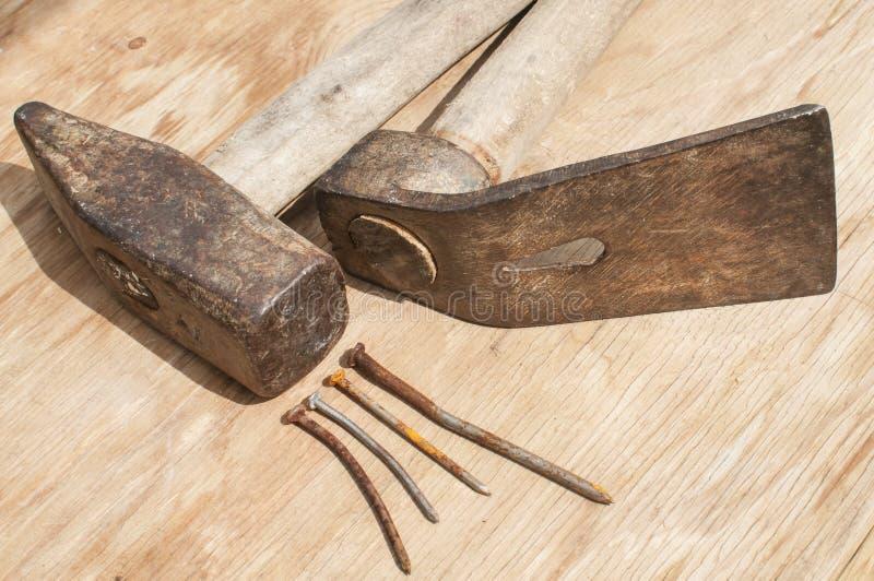 Oude hamer, adze en roestige spijkers stock afbeeldingen
