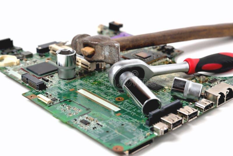 Oude hamer en een moersleutel op een oude microschakeling voor een computer  stock foto's