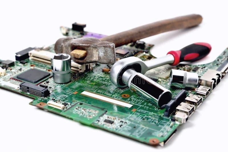 Oude hamer en een moersleutel op een oude microschakeling voor een computer  royalty-vrije stock afbeelding