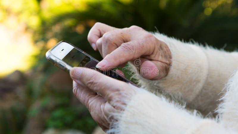 Oude handen van grootmoeder die een mobiele telefoon in het tuinhuis houden royalty-vrije stock afbeelding