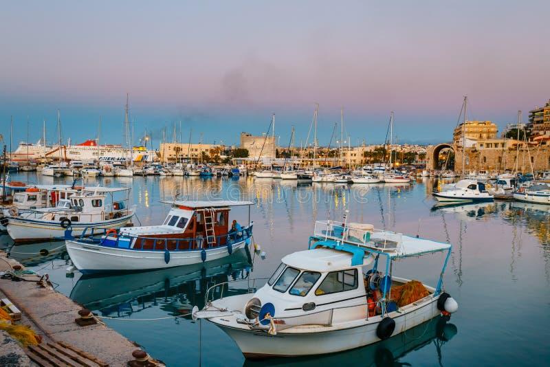 Oude haven van Heraklion met vissersboten en jachthaven tijdens schemering, Kreta, Griekenland stock fotografie