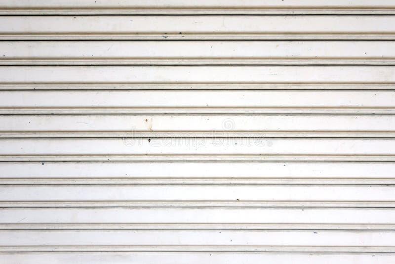 Oude het blinddeur van de witmetaalrol, de close-up golfachtergrond van de staalplaattextuur stock afbeelding