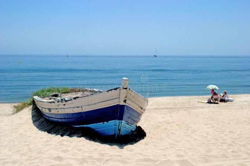 Oude het roeien boot op zonnig wit zandig strand stock afbeelding