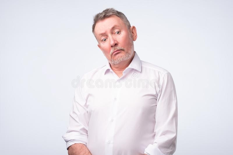 Oude hogere mens in wit overhemd met ernstige en droevige uitdrukking stock foto