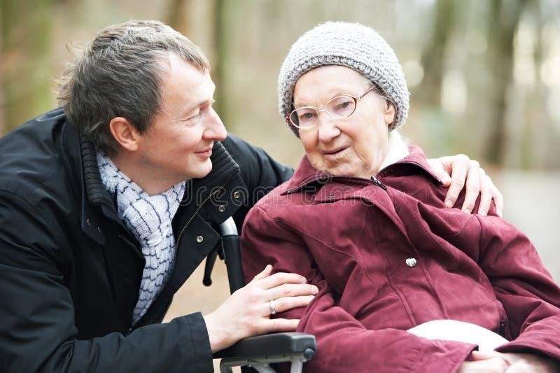 Oude hogere vrouw in rolstoel met zorgvuldige zoon stock foto