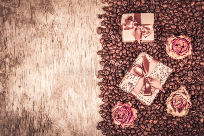 Oude houten achtergrond, koffiebonen en giftdozen Gift met lint en boog, droge rozen en koffie Romantisch concept Koffie royalty-vrije stock afbeeldingen