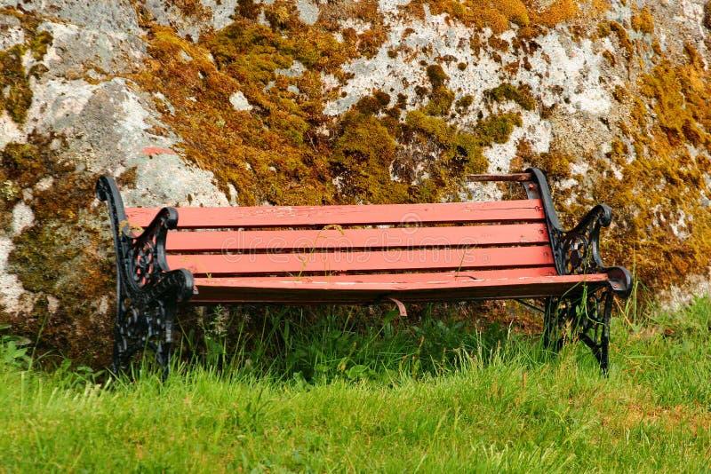 Oude houten bank op groen gras dichtbij de mos behandelde steen stock foto's