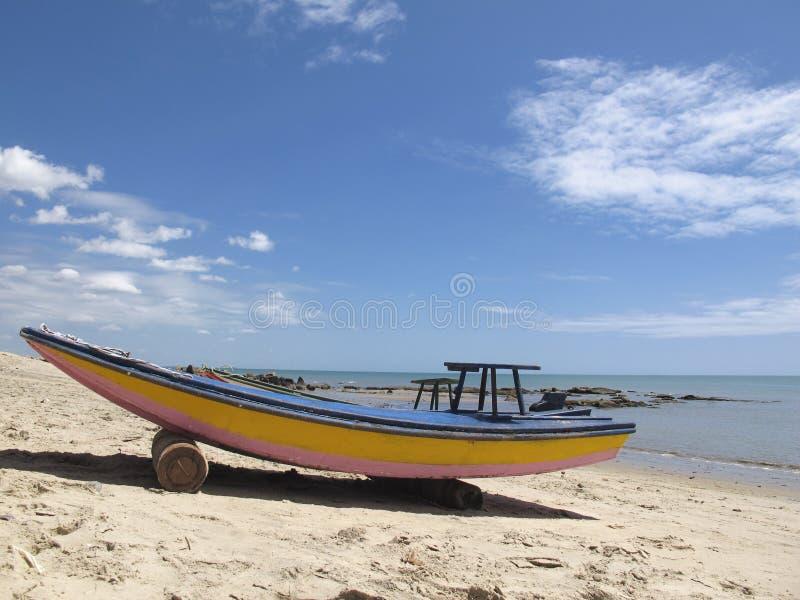Oude houten boot in blauwe en gele kleuren, op wit strand met blauwe hemel - Fortaleza, Ceara, Brazilië royalty-vrije stock foto